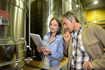 Winemaker with client in winery looking at electronic tablet photo