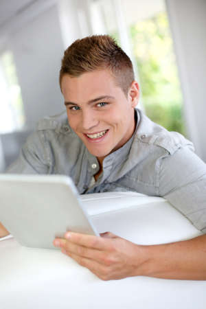 Young man using electronic tablet at home photo