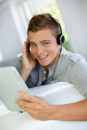 Young man listening to music with digital tablet photo
