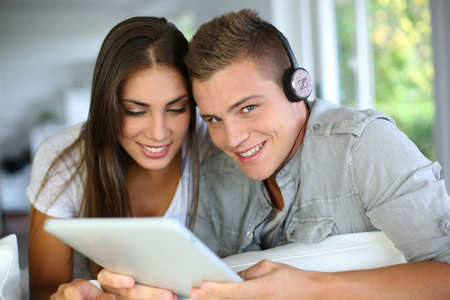 Young couple listening to music on electronic tablet photo