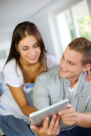 Young couple websurfing on electronic tablet photo