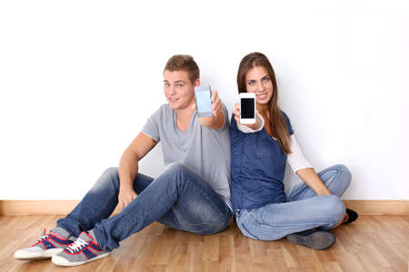 Teens showing mobile phones to camera photo