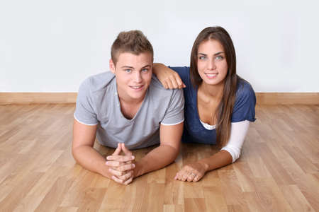 Cute young couple laying on wooden floor photo