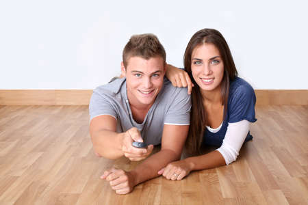 Cheerful young couple using tv remote control photo