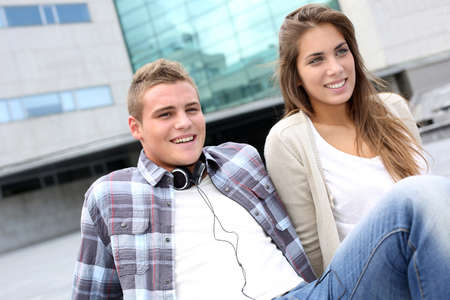 Young couple sitting outside the college building photo