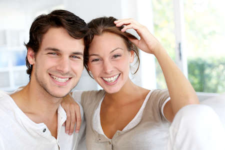 Portrait of smiling young couple at home photo