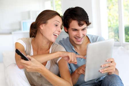 people watching tv: Cheerful couple choosing tv program on digital tablet