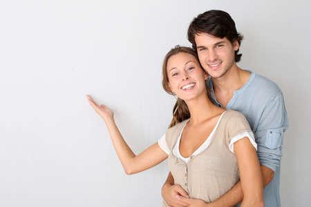 couple enlac�: Jeune couple sur fond blanc d�signant un message