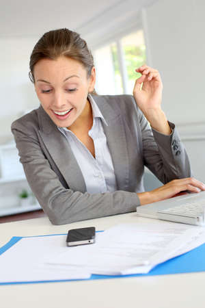 Smiling businesswoman sitting at her desk Stock Photo - 15279606