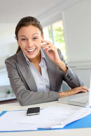 Smiling businesswoman sitting at her desk photo