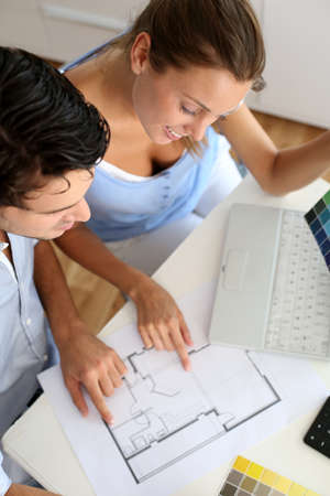 Upper view of couple looking at blueprint photo