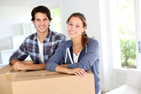 Smiling couple leaning on boxes in new home photo