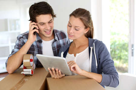 packing boxes: Couple calling transport company to move in new house