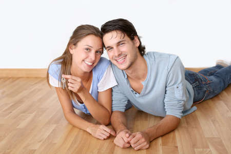 Cheerful couple laying down wooden floor photo