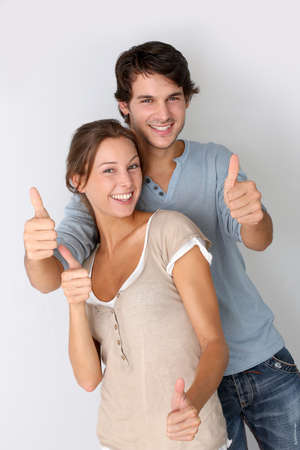 portrait young girl studio: Cheerful couple showing thumbs up, isolated Stock Photo