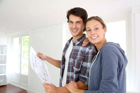 family moving house: New property owners looking at home blueprint Stock Photo