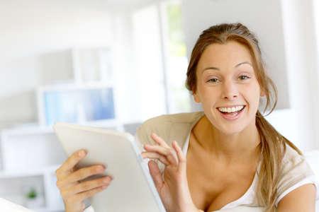 Beautiful smiling woman using digital tablet at home