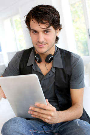 Handsome guy listening to music on internet with tablet photo
