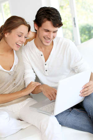 websurfing: Happy young couple using laptop computer at home
