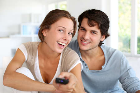 at home: Couple sitting in sofa with remote control in hands Stock Photo