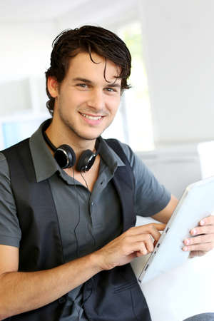 hombres jovenes: Chico guapo escuchar música en internet con tableta Foto de archivo