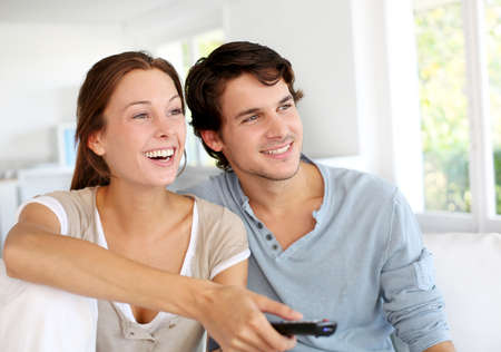 Couple sitting in sofa with remote control in hands Stock Photo