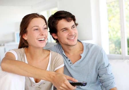 pareja viendo tv: Pareja sentada en el sof� con el mando a distancia en las manos