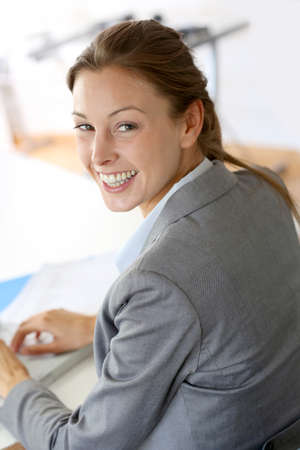 telework: Smiling businesswoman sitting at her desk