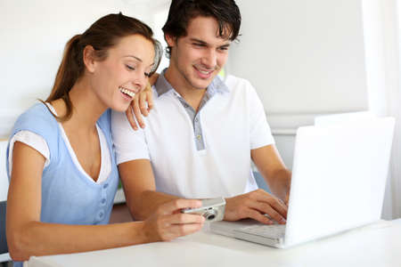 Couple at home uploading photographies on internet photo