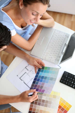 Upper view of couple looking at colour chart photo