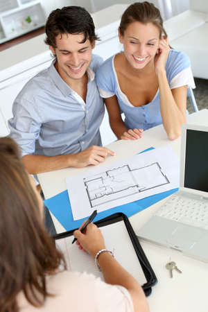 real estate planning: Couple meeting architect for plans of future home Stock Photo