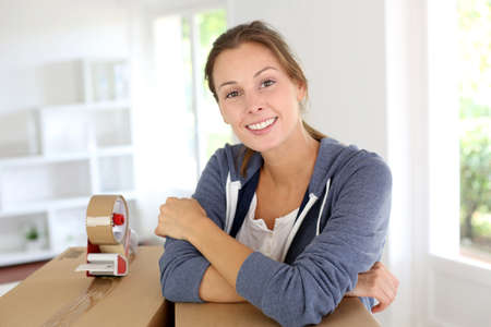 packing tape: Smiling young woman packing boxes to move out