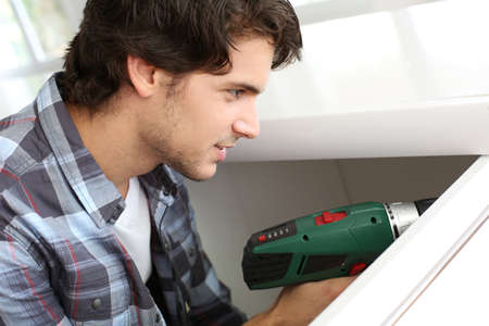 electric drill: Repairman fixing door with electric drill