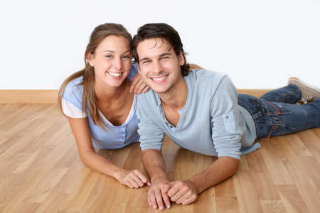 wooden floor: Cheerful couple laying down wooden floor