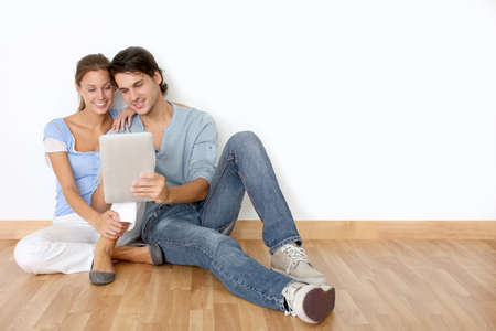 Couple using tablet laying on the floor at home photo