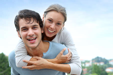 Man giving piggyback ride to girlfriend outside Stock Photo