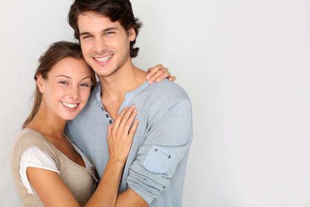 pareja abrazada: Alegre joven pareja de pie sobre fondo blanco, aislado