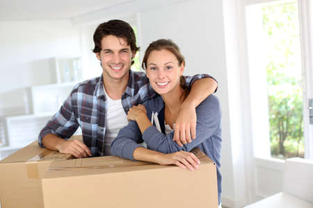 packing boxes: Smiling couple leaning on boxes in new home