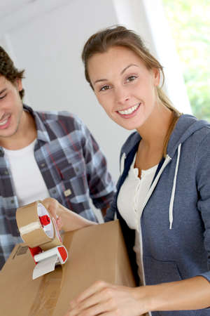 Smiling young woman packing boxes to move out photo