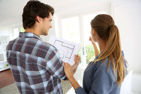 construction plans: New property owners looking at home blueprint Stock Photo