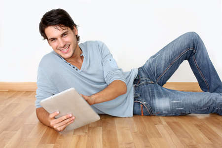 Young man laying on the floor with digital tablet photo