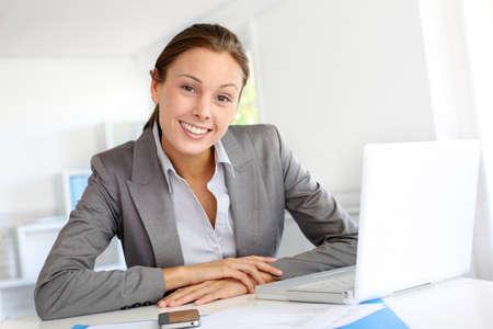 telework: Smiling businesswoman sitting at her desk