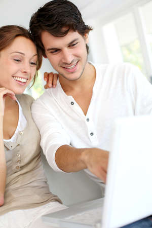 Happy young couple using laptop computer at home photo