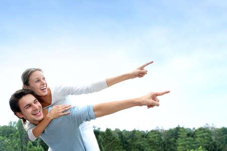 carrying girlfriend: Man giving piggyback ride to girlfriend outside Stock Photo