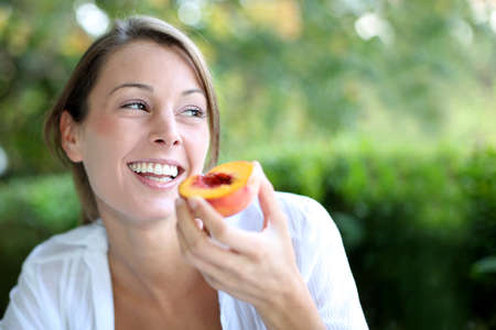 eating in the garden: Smiling woman eating peach for breakfast