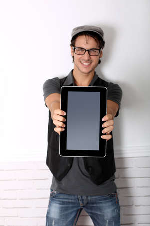 Smart guy showing tablet screen toward camera