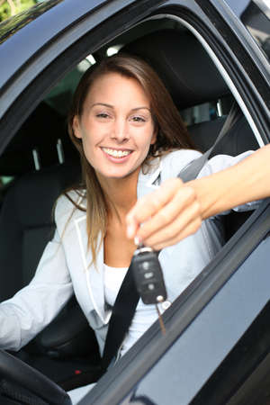 new automobiles: Cheerful girl holding car keys from window