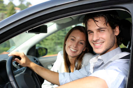 the car window: Cheerful couple driving car