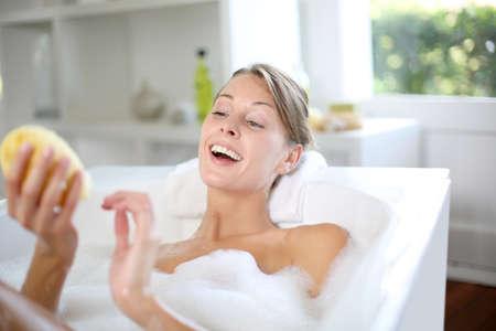 beautycare: Beautiful woman using bath sponge