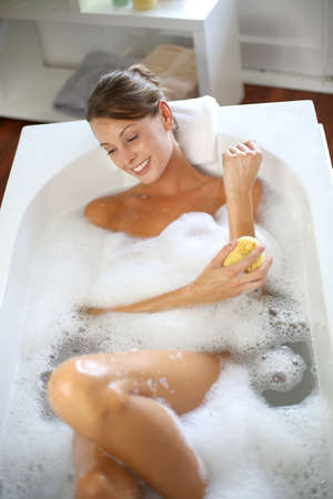 Beautiful woman using bath sponge photo